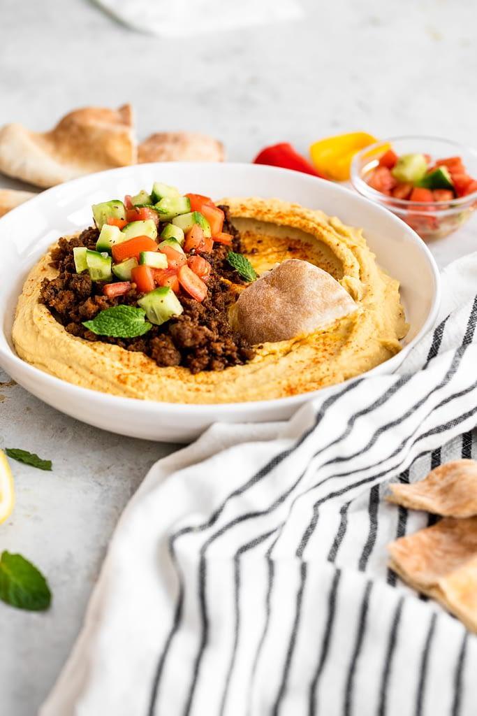 loaded hummus recipe 45 degree angle, pita digging into hummus