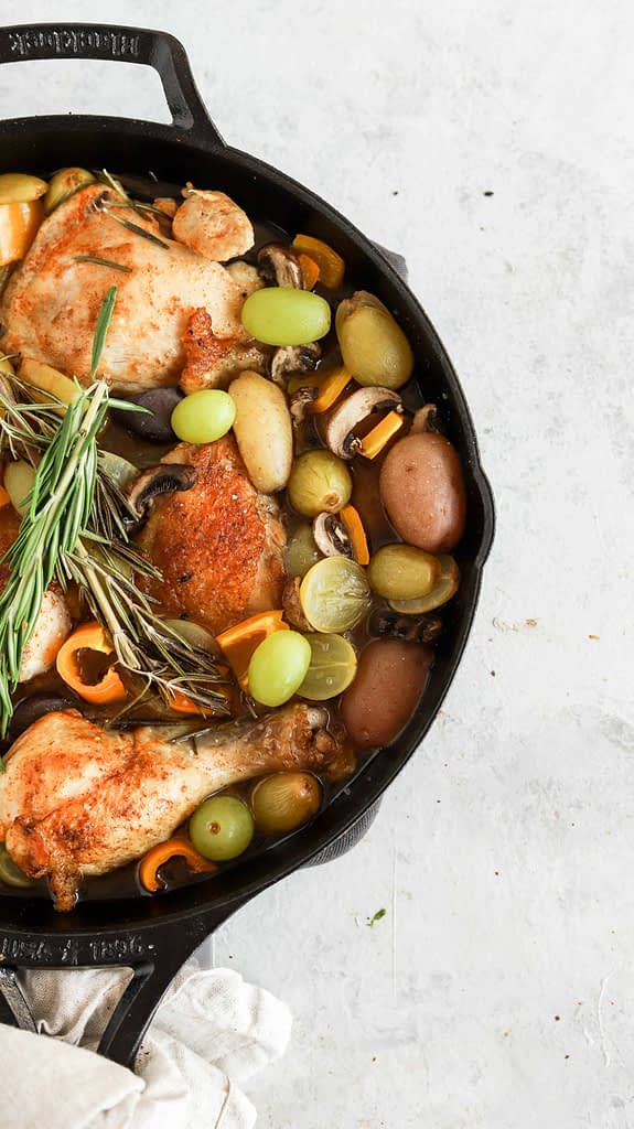 Chicken in cast iron skillet with grapes, potatoes and rosemary.