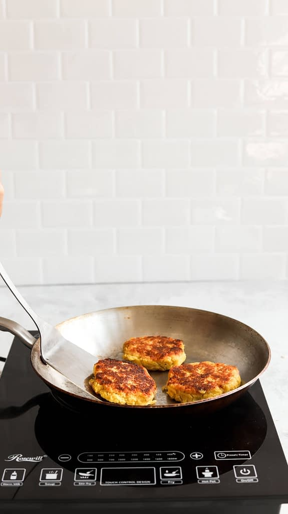 Plantain Recipe: Burgers in pan about to be flipped with spatula